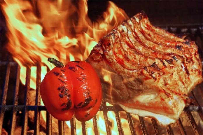 Ein Steak und eine Tomate auf einem brennenden Grill