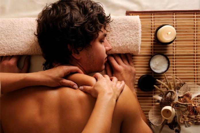Ein Frau massiert einen Mann in entspannter Atmosphäre