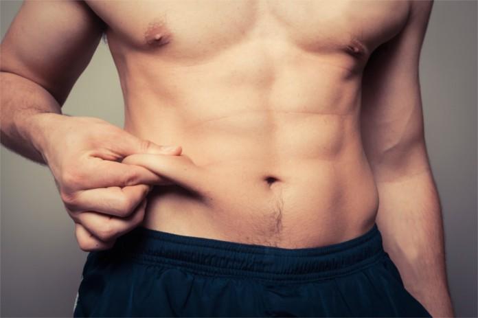Ein ansonsten fitter Mann kneift sich in seinen Bauchspeck