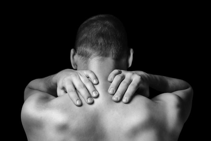 Man massiert sich seinen Muskelkater am Rücken