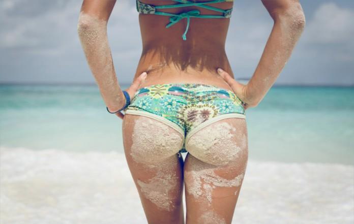 Trainierter, sandiger Arsch einer Frau am Strand
