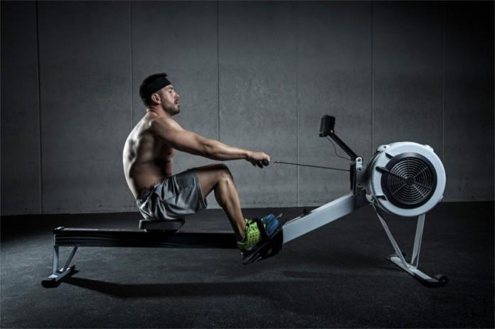 Ein durchtrainierter Mann sitzt auf einem Rudergerät