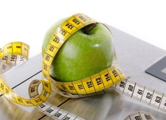 Eine Waage auf der ein mit einem Maßband umschlungener Apfel liegt
