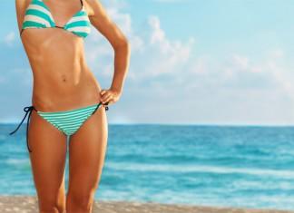 Eine schlanke Frau mit einer sehr gutem Figur steht am Strand