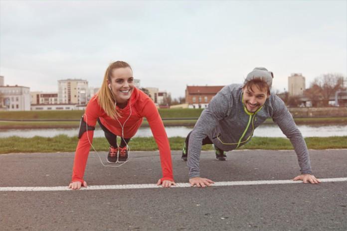 Eine Frau und ihr Trainingspartner machen zusammen Liegestütze