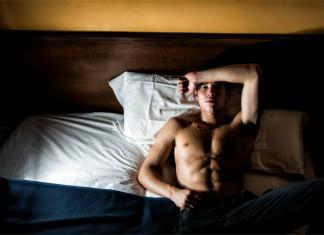 Ein trainierter Mann liegt mit offenen Augen im Bett