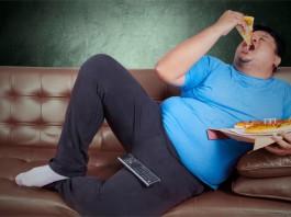 Ein dicker Mann auf dem Sofa der eine Pizza isst
