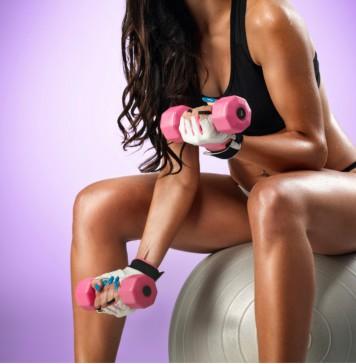 Eine Frau sitzt auf einem Gummiball und trainiert mit Hanteln