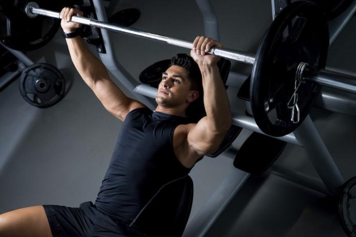 Sportler mit Langhantel trainiert seine Brustmuskeln
