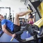 Sportler im Fitnesscenter trainiert an der Beinpresse