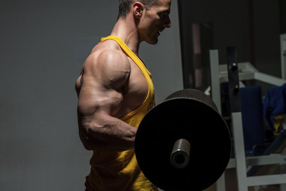Sportler trainiert Oberarmcurls mit der Langhantel