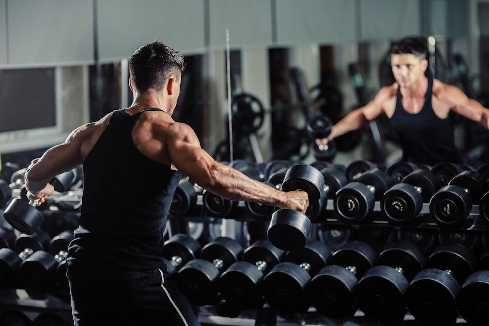 Sportler im Fitnesscenter trainiert mit Kurzhanteln