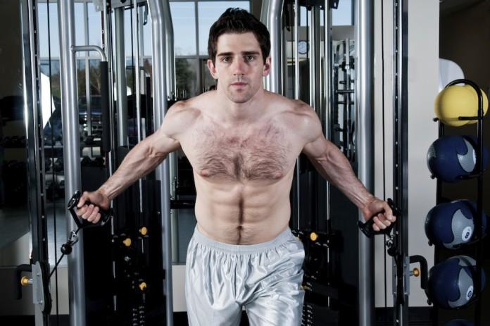 Sportler im Fitnesscenter trainiert am Kabelzug