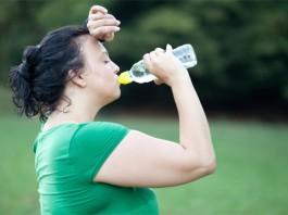 Eine dickere Frau schwitzt nach dem Training und trinkt Wasser