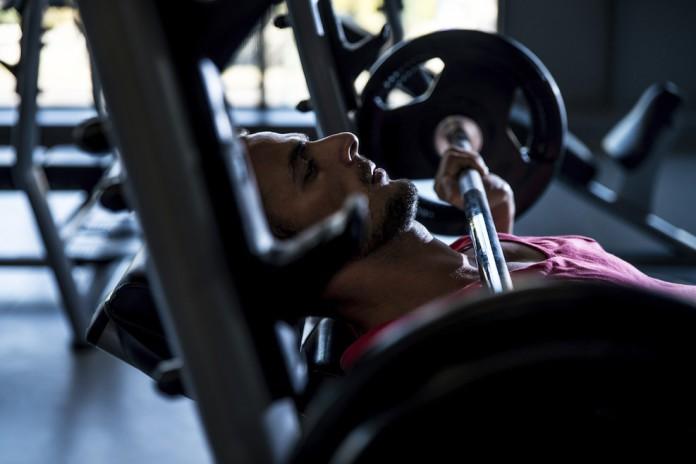 Sportler auf der Trainingsbank hält die Langhantel eng