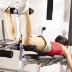 Sportlerin trainiert das Beinbeugen an einer Trainingsmaschine