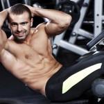 Sportler trainiert seine seitlichen Bauchmuskeln mit Cross-Crunches