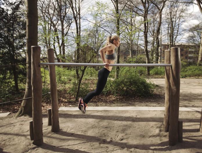 Sportlerin trainiert Dips zur Brust auf einem Barren