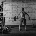 Sportler trainiert im Gym mit einer Langhantel