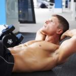Junger Mann trainiert seine Bauchmuskeln mit geraden Crunches