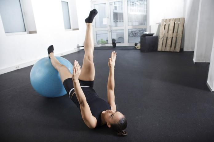 Sportlerin trainiert auf dem Boden halbe Klappmesser