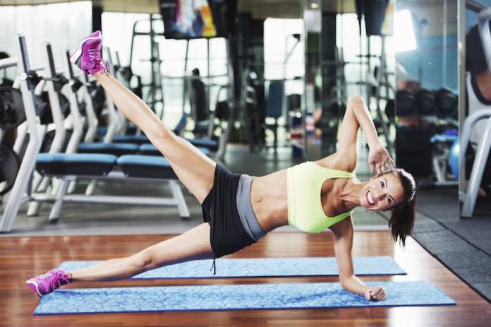 Sportlerin trainiert den Hiplift auf der Seite im Fitnessstudio
