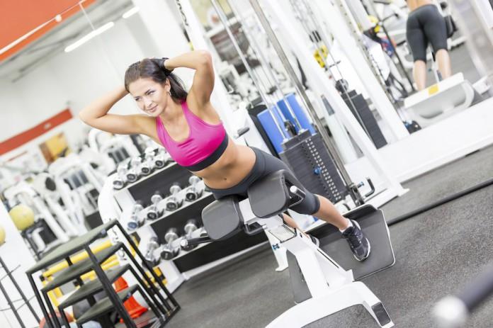 Sportlerin trainiert Hyperextensions auf einer Bank