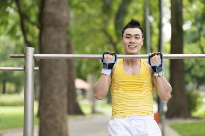 Sportler trainiert Klimmzüge an einer Reckstange im Freien
