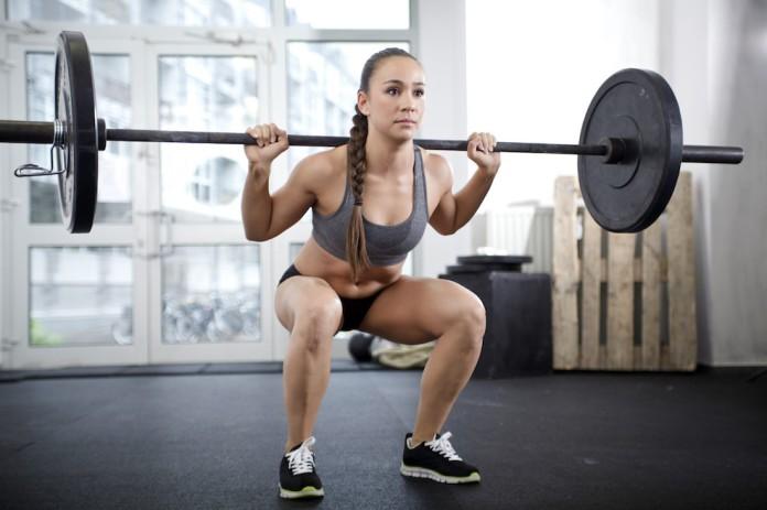 Sportlerin trainiert mit der Langhantel Kniebeugen