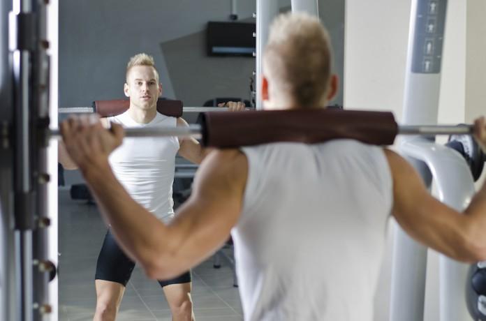 Sportler trainiert an der Multipresse Kniebeugen