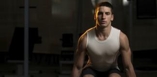 Sportler trainiert Kniebeugen mithilfe der Kurzhantel