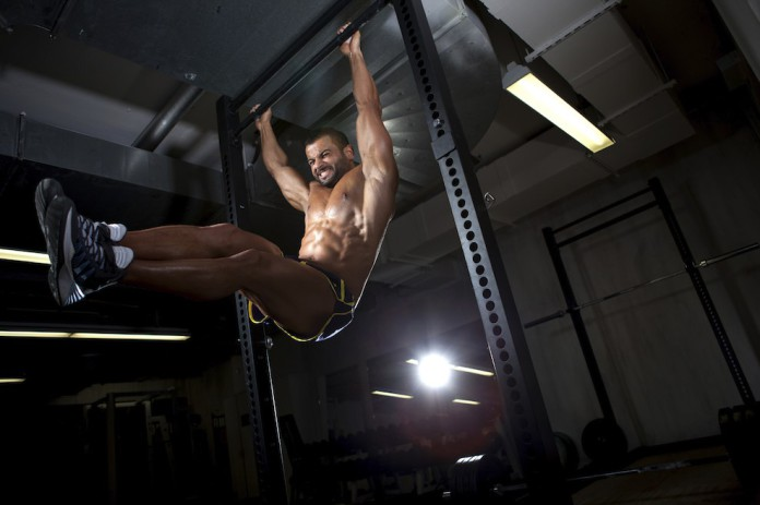 Sportler hebt seine Beine an der Klimmzugstange hängend