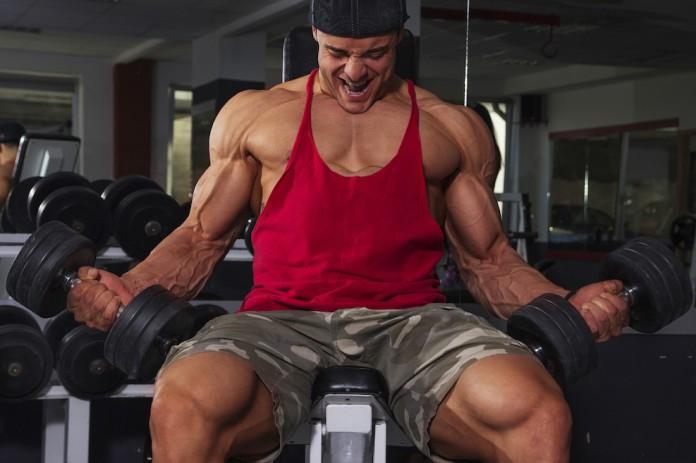 Sportler auf einer Schrägbank trainiert Kurzhantel-Curls