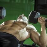 Sportler auf einer Negativbank trainiert mit Kurzhanteln