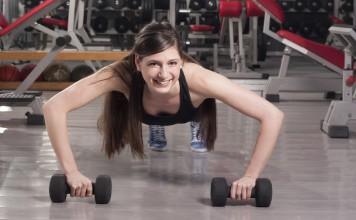 Sportlerin im Fitnesscenter rollt sich mit Kurzhanteln auf dem Boden und trainiert so Ihre Bauchmuskeln.