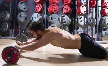 Sportler im Fitnesscenter rollt auf einer Langhantel