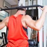 Sportler trainiert am Latzug den Nacken