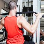 Sportler trainiert am Latzug seine Brustmuskeln