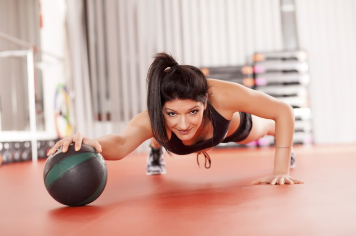 Sportlering trainiert Liegestütze auf einen Medizinball