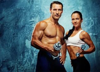 Ein trainierter Mann und eine fitte Frau jeweils mit einer Hantel in der Hand