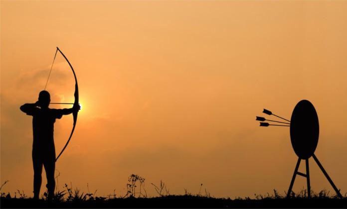 Man sieht einen Mann mit einem Bogen, der auf eine Zielscheibe schießt
