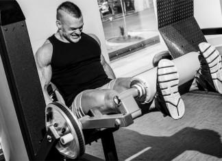 Ein Bodybuilder hebt ein Gewicht mit letzter Kraft und schmerzverzerrtem Gesicht