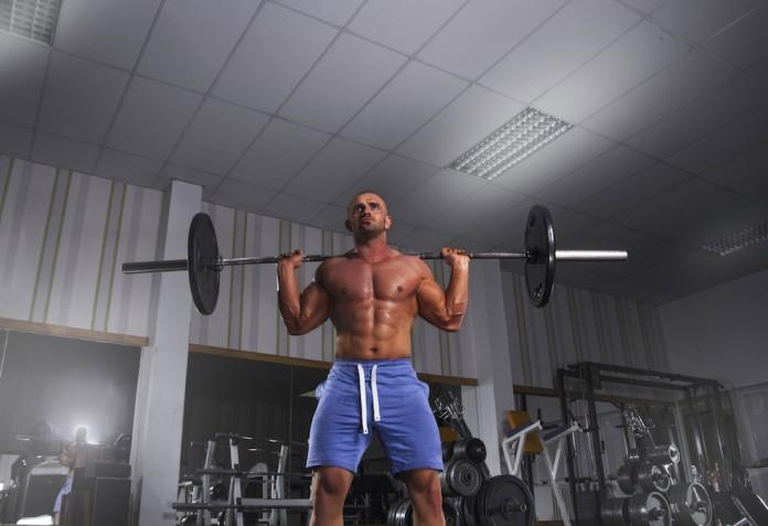 Sportler trainiert das Nackendrücken mit der Langhantel