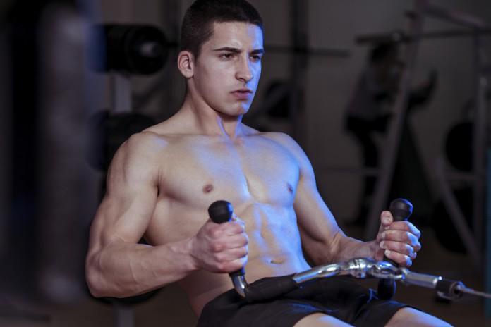 Sportler trainiert an einer Zugmaschine rudern.