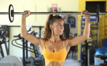 Sportlerin mit einer Langhantel trainiert die Schulterpartie