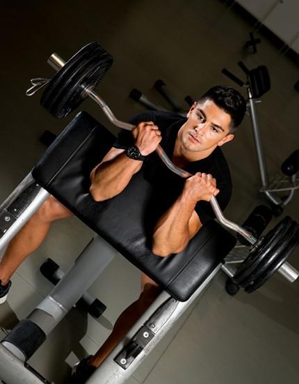 Sportler im Fitnessstudio trainiert an der Larry-Scott-Bank