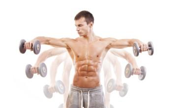 Sportler trainiert mit 2 Kurzhantel das Seitenheben