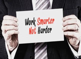 """Ein Manager hält ein Schilder mit der Aufschrift """"Work Smarter not Harder"""""""
