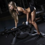Sportlerin trainiert Trizeps-Kickbacks auf einer Bank