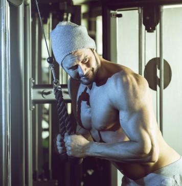Sportler trainiert an einem Kabelzug seinen Trizeps